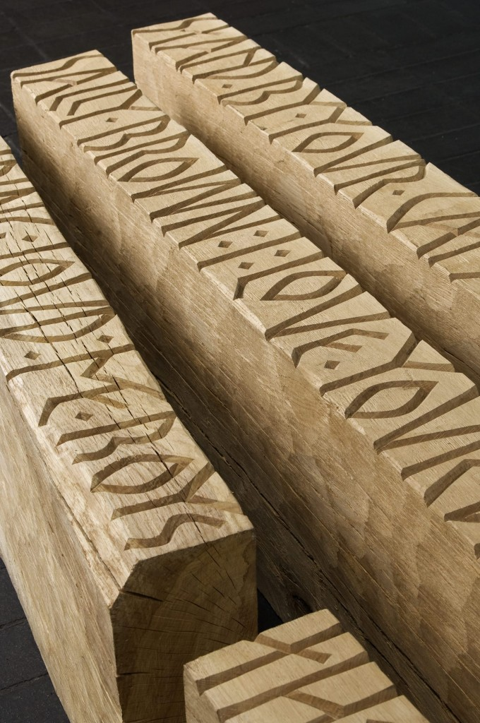 large oak timbers with deeply carved runic style inscriptions